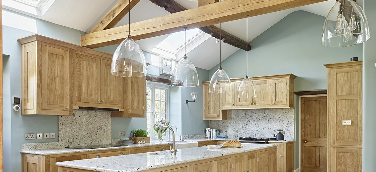 Clear glass globe pendant light over kitchen island in shaker style kitchen within farm house setting