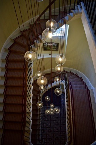 Hereford Globe pendant light cluster chandelier in a spiral stair case