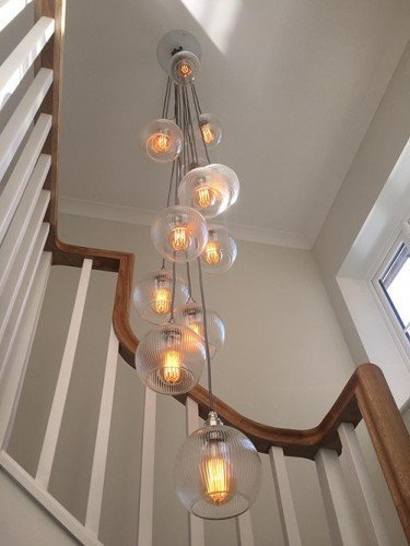 A custom made cluster chandelier using Skinny Ribbed Hereford shades hung in a double height stairwell creating a great feature light