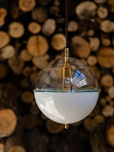 Glass globe Grafton pendant light with clear top and white bottom in Polished Brass against fire wood