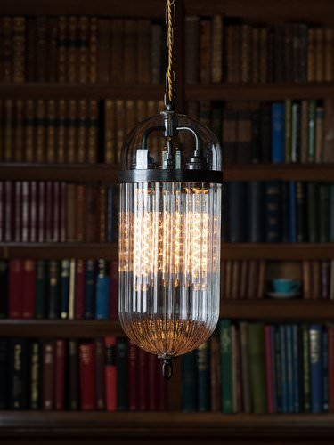 The Aston lantern shown here lighting a library features clear and ribbed handblown glass with a bronze finish