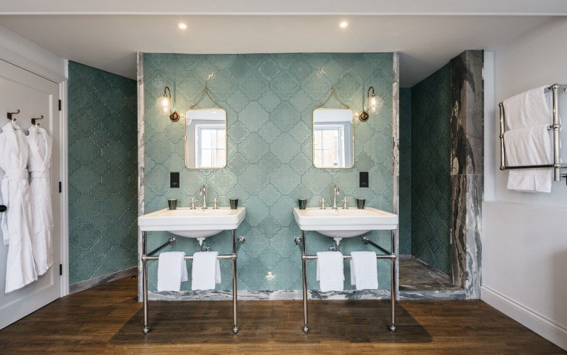 Stunning bathroom at The Bower House lit with our Hereford Glass Globe Swan Neck Wall Lights for bathrooms.