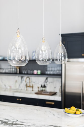 Wellington pendant lights hung 3 a line over a kitchen island