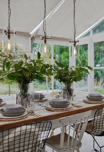 Clear glass Sellack lanterns hung, 3 in a row, over dining table