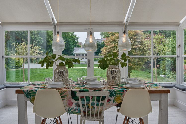 Wellington pendant lights hung over dining table featuring skinny ribbed glass shades.