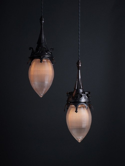 A pair of Gothic style pendant lights with Holophane shades